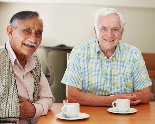 Three senior men enjoying some coffee together in the retirement home